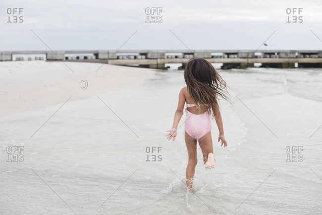 Girl running in shallow sea water