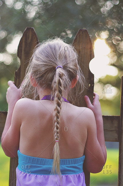 Girl wearing braids peeks through a fence