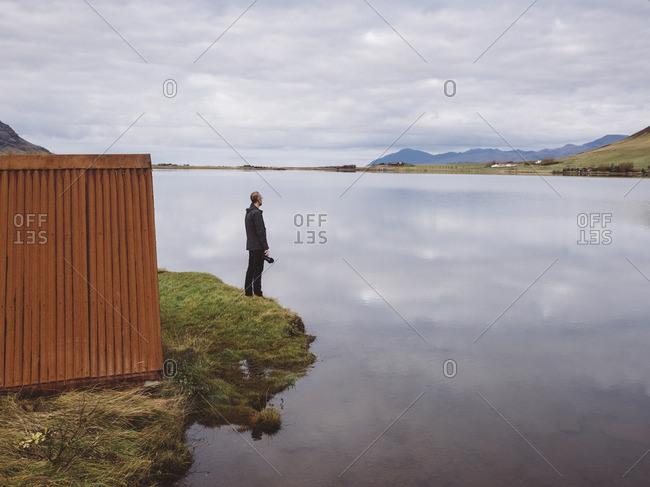 Man looking out over Lake Medalfellsvatn in Hvalfjordur, Iceland