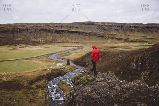 Person overlooking Brynjudalur in Hvalfjordur, Iceland