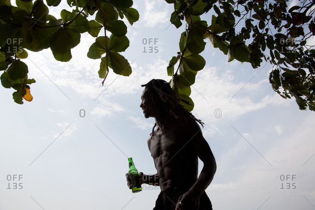 Robertsport, Liberia - February 14, 2008: Man with a beer standing under a tree