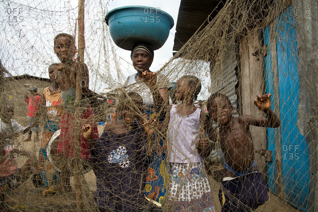 Monrovia, Liberia - February 15, 2008: Woman and children standing behind nets at a fish market
