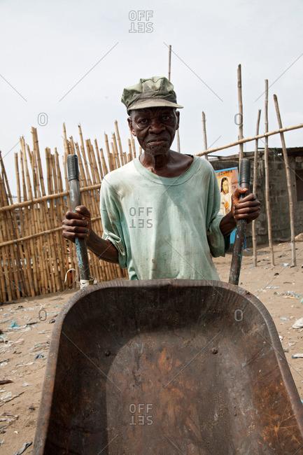 Monrovia, Liberia - February 15, 2008: Old man pushing a wheelbarrow