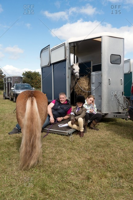 Kinross, Scotland - August 13, 2016: Father and daughters relaxing on a horse trailer