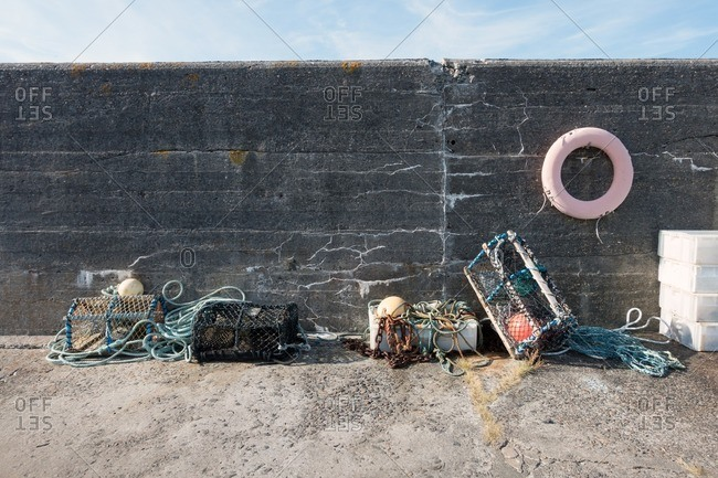 Lobster and crab pots, nets, and buoy sitting against a seawall
