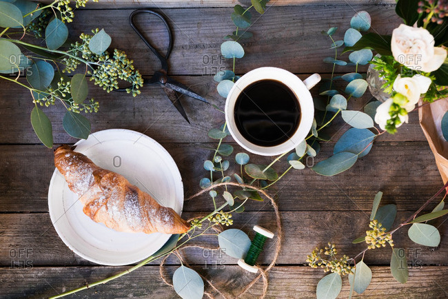 Coffee, pastries and greenery on a rustic wooden table