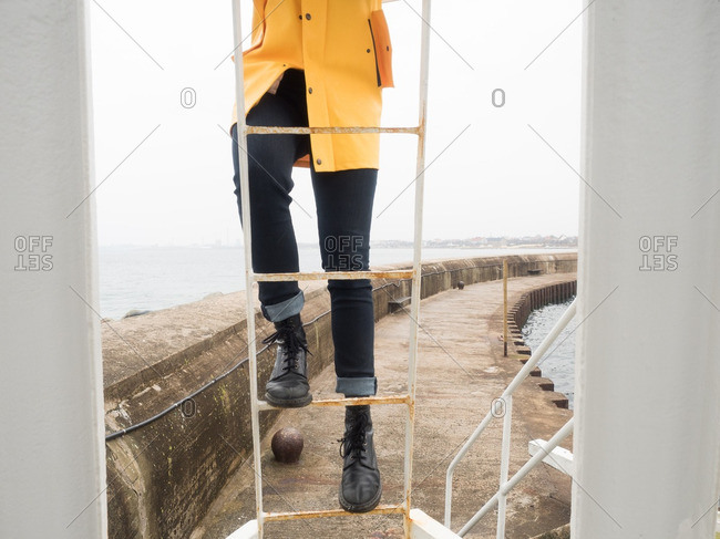 Person in a yellow raincoat climbing a ladder on a seawall