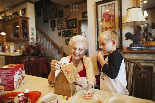 Boy watches his grandmother decorate a gingerbread house