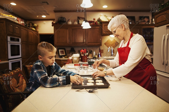 Boy helping grandmother bake cookies in kitchen