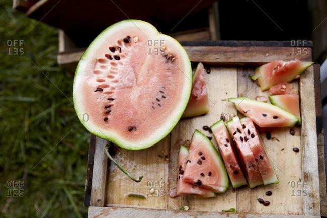 Fresh watermelon cut on a wooden crate on a farm