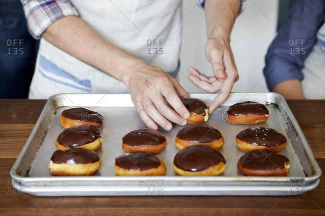 Hands placing chocolate glazed doughnuts on tray