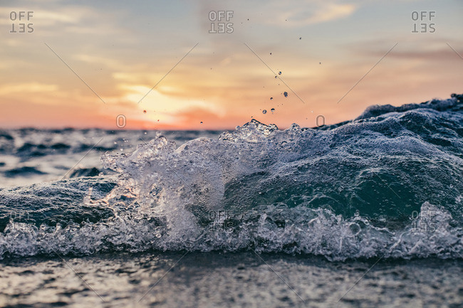 Splashing waves on a lakeshore at sunrise