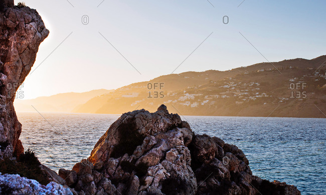 Sun setting over a rocky coast in Granada, Spain