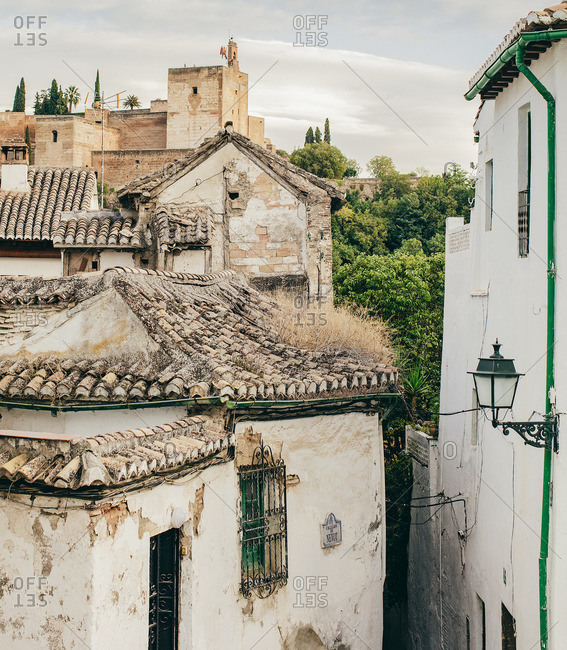 Granada, Spain - September 21, 2015: Traditional rooftops and a distant castle