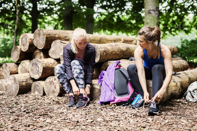 Young women wearing sports shoes while sitting on logs at park