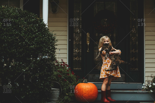 Little girl holding cat on her front steps
