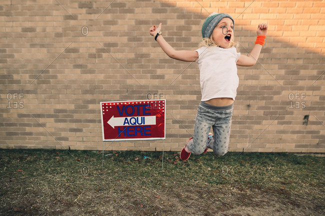 "Little girl standing by a ""Vote Here"" sign"