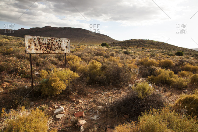 Wasteland landscape with broken sign and distant mountains