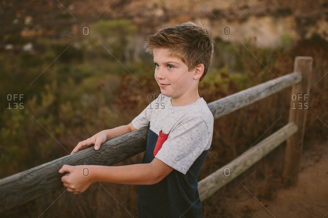 Boy holding a wooden fence on a trail