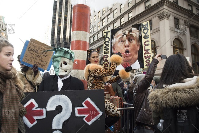 New York City, New York - November 12, 2016: Woman dressed as a cat slicing a poster of Donald Trump an anti-Trump rally in New York City