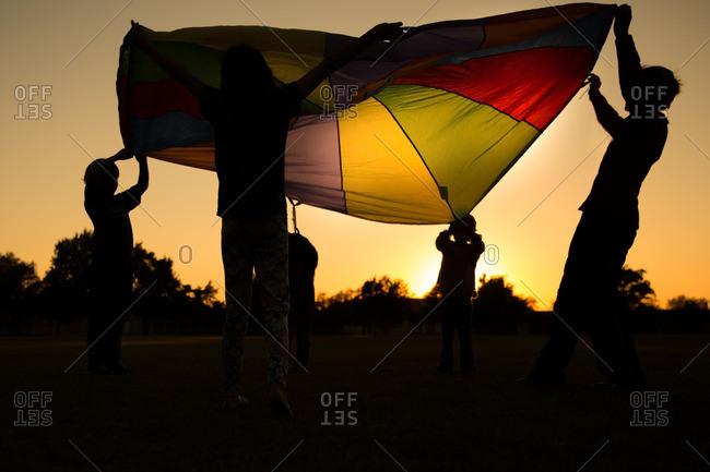 Kids holding up a parachute