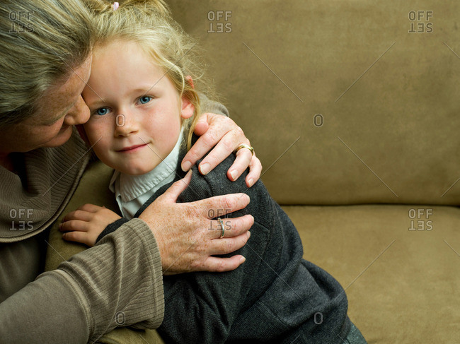 A Young Girl Being Hugged By Her Mum