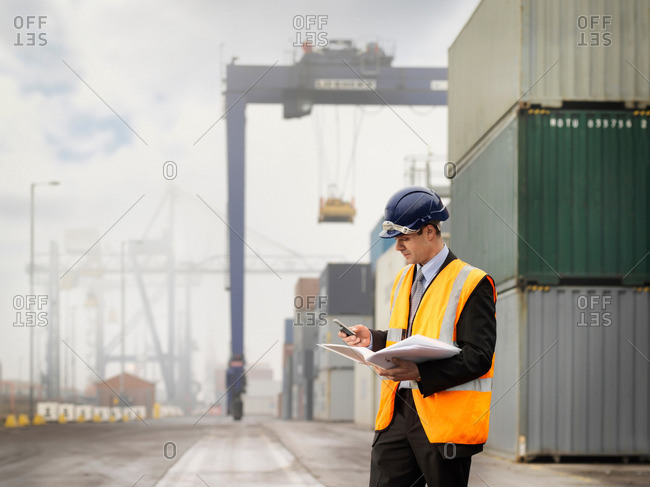 Businessman In Port With Containers