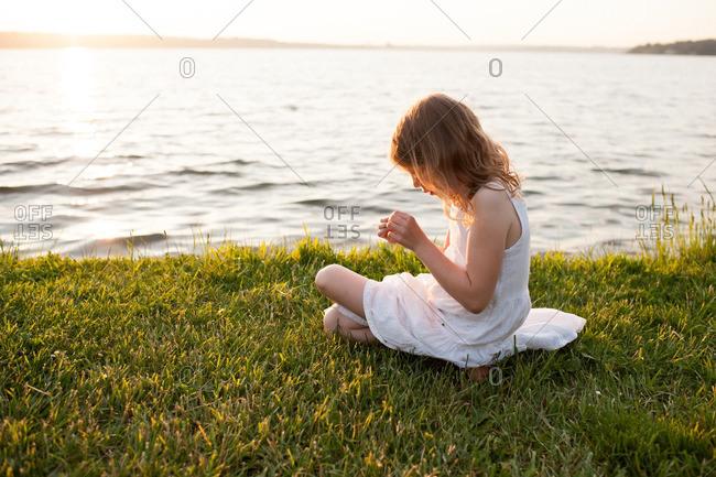 Girl sitting in grass on coast