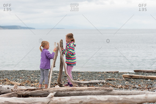 Girls with logs on a beach