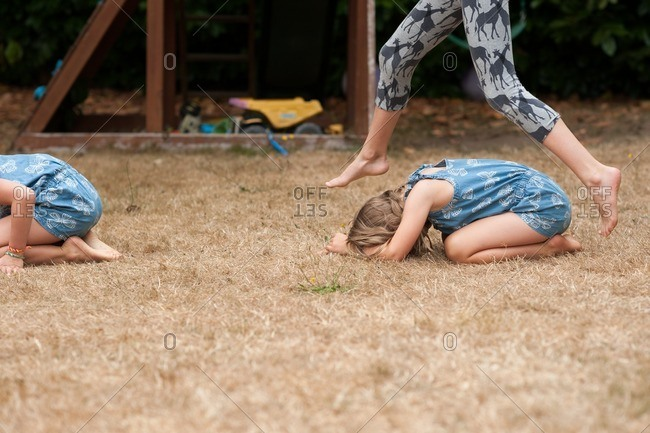 Girls playing leapfrog in yard