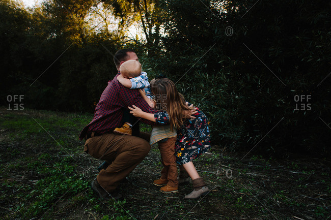 Dad hugging kids in rural setting