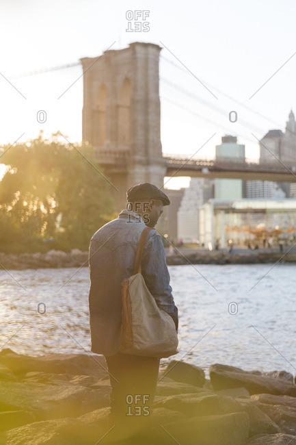 Man by river near Brooklyn Bridge
