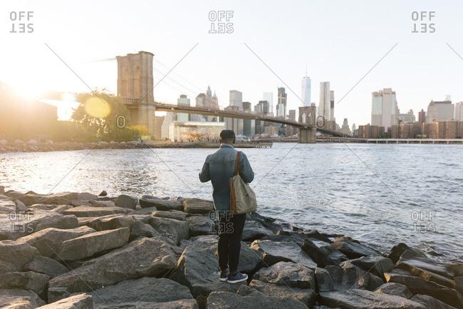 Man on boulders near Brooklyn Bridge