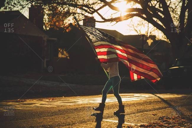 Girl carrying American flag in street