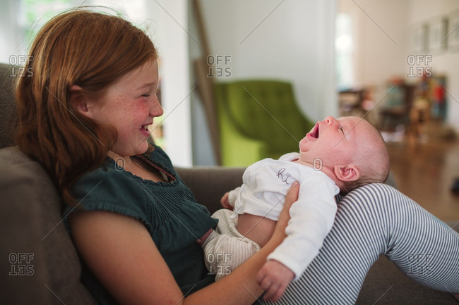 Girl holding a yawning baby