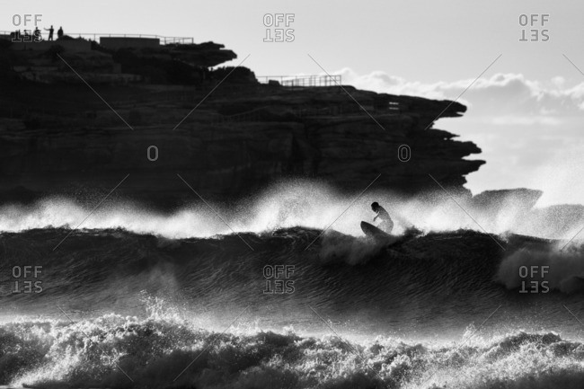 Silhouette of surfer at dawn in black and white, in the bay of Bondi Beach, one of the most famous beaches in Sydney, Australia