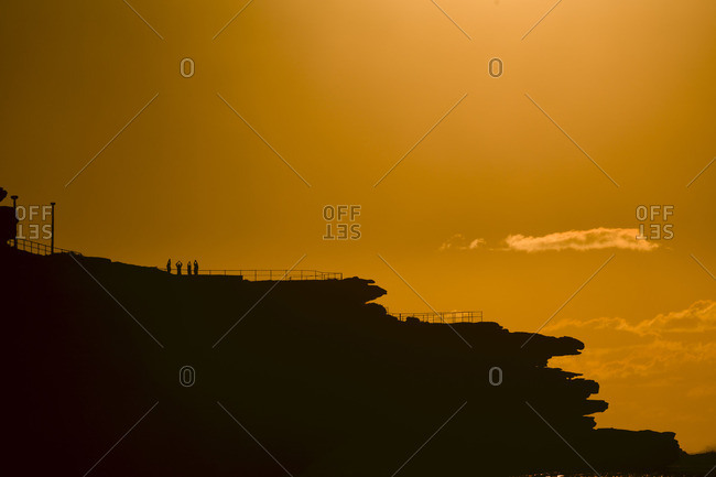 Sunrise at Bondi Beach in Sydney, one of the most famous beaches in Australia, with the sky yellow and orange with silhouettes of rocks and people