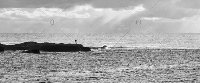 Man standing and fishing on a rock in the bay of Bondi Beach, one of the famous beaches in Sydney, Australia