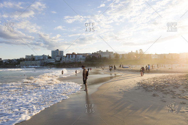 Sydney, Australia - September 24, 2016: People enjoying the last sunrays at sunset in Bondi beach, one of the most famous beaches