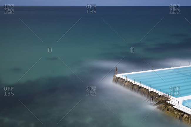 Long exposure image of an unidentified woman standing at the corner of a swimming pool, being part of the ocean in Bondi Beach, Sydney, Australia