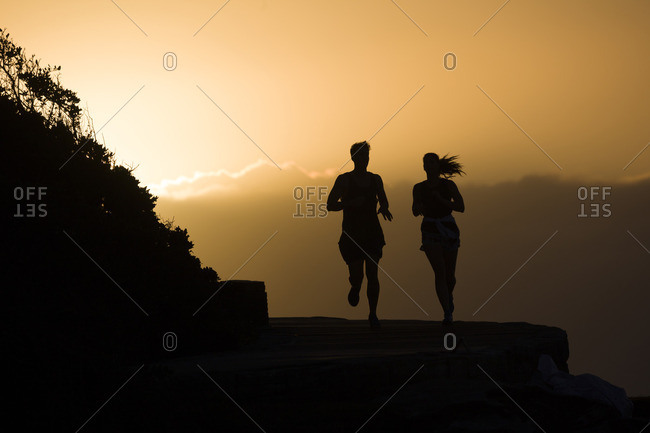 Silhouettes of a couple of man and woman running along the coastline in Sydney