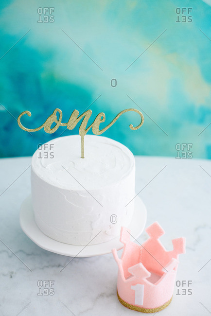 One cake topper on white cake against teal background