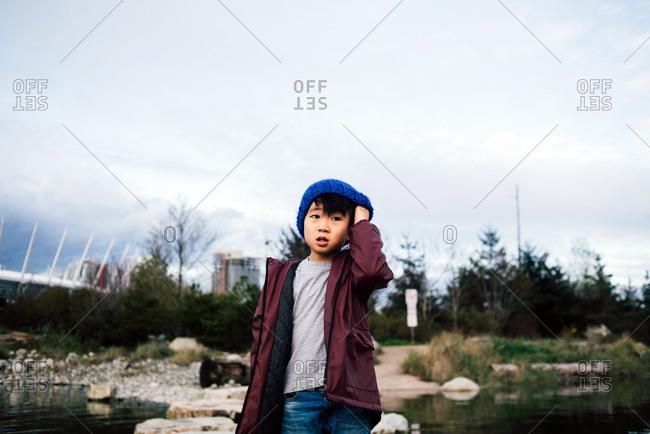 Boy scratching itchy head under blue toque