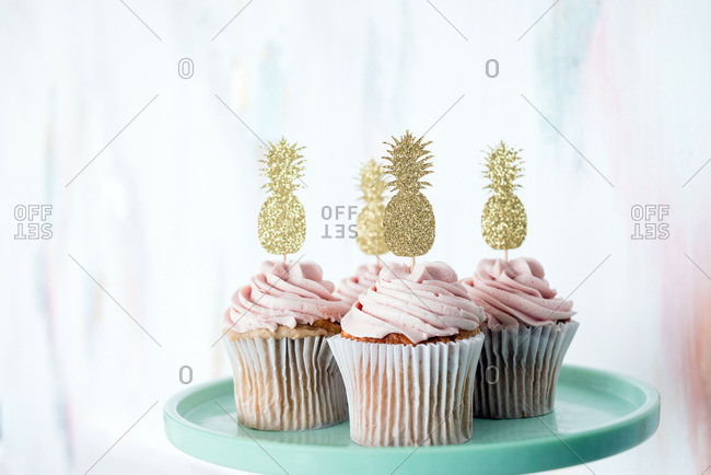 Cupcakes with pink frosting and pineapple toppers on teal cake stand