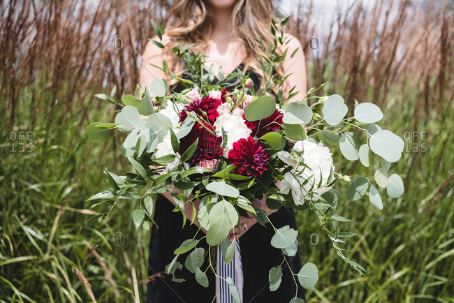 Young lady holding pretty bouquet of flowers in a field