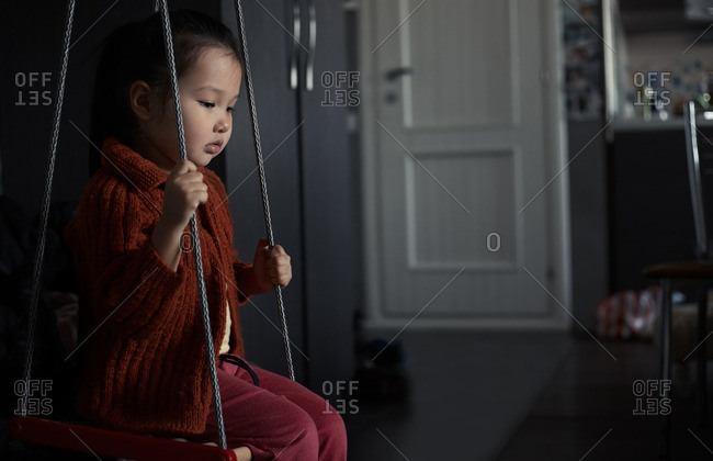 Sad girl on a rope swing at home