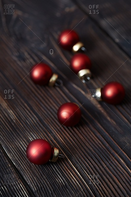 Red Christmas bulbs on a wooden background