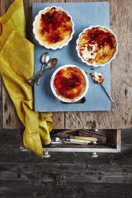 Three dishes of vanilla creme brulee on table