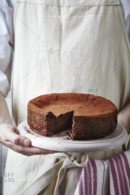 Person holding a chocolate cheesecake