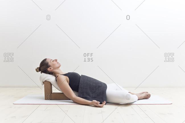 Girl in restorative yoga posture using blocks